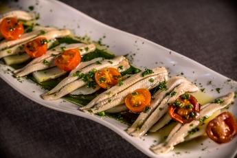 Foto de sardina ahumada con tartar de aguacate y tomate cherry