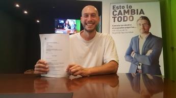Foto de Tomas Peñato mostrando el documento que le cancela de todas