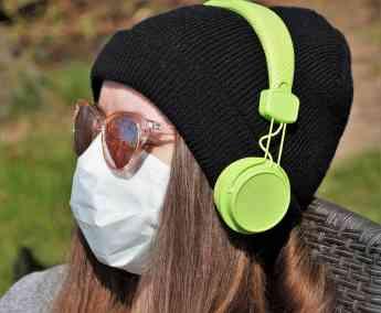 Una chica con mascarilla esucha música