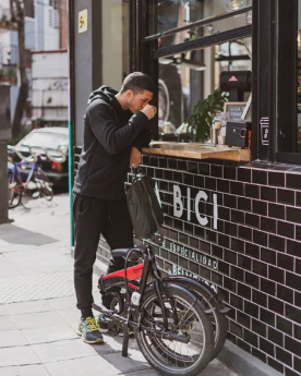 Ciclista urbano plegable disfrutando de su espresso