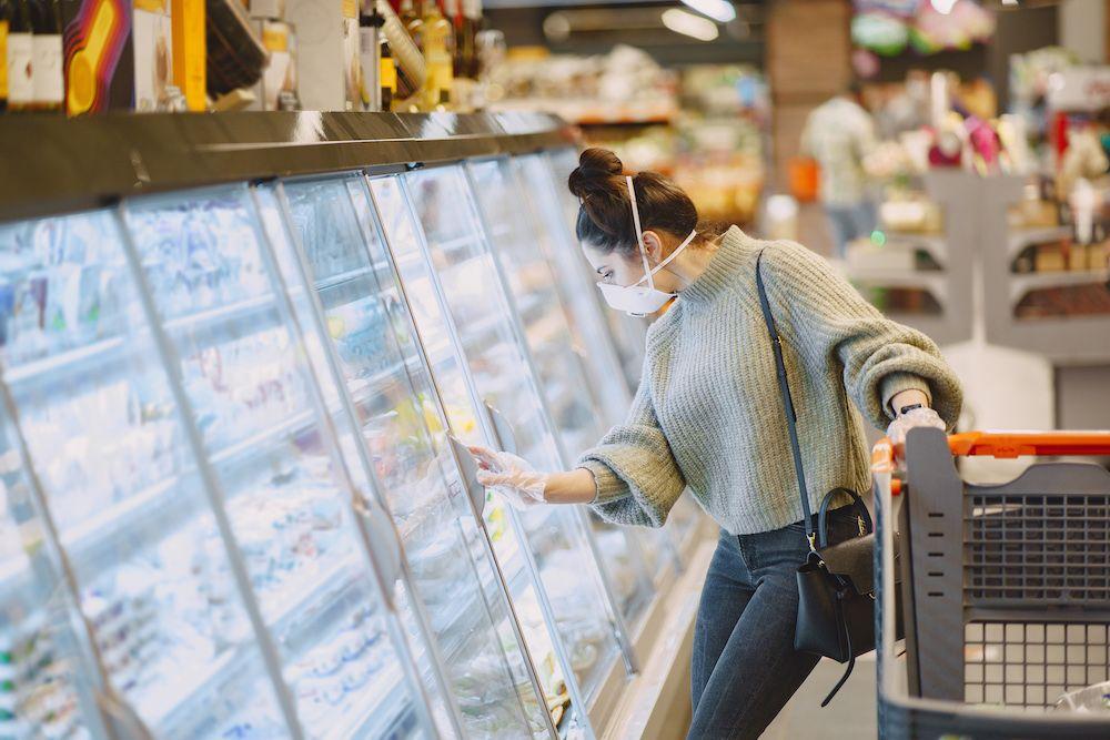 Foto de Mujer haciendo la compra con medidas de protección contra el