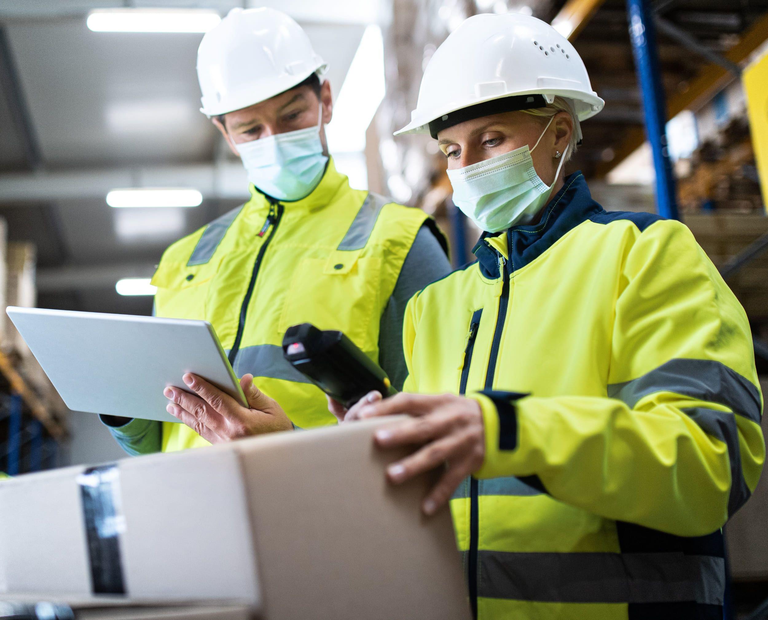 Fotografia Trabajadores de almacén con mascarillas y cascos