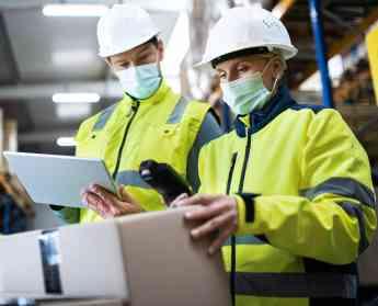 Foto de Trabajadores de almacén con mascarillas y cascos
